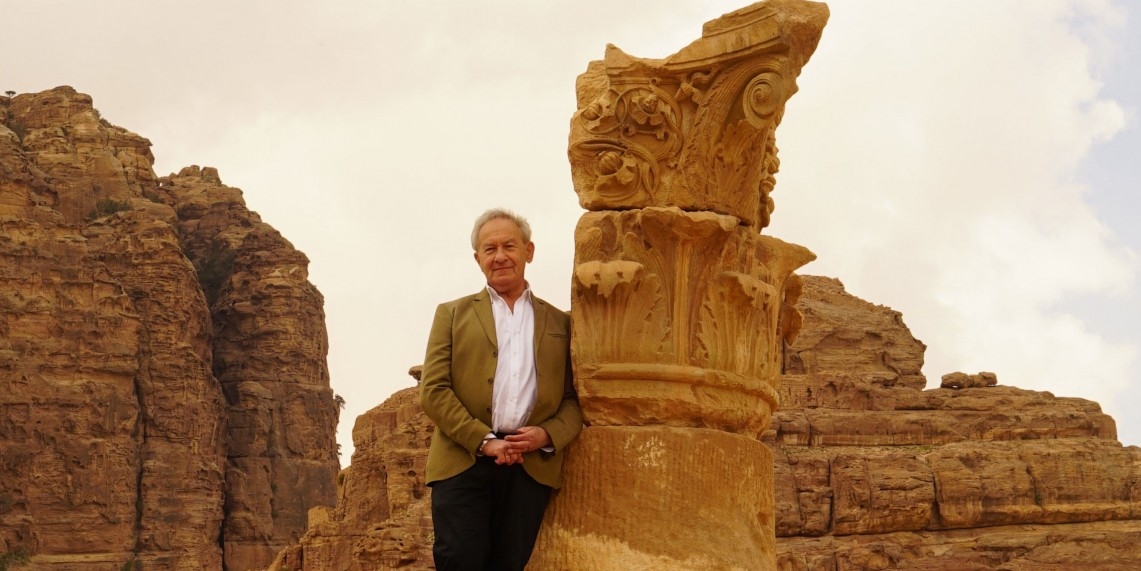 host standing in front of ancient carved column and mountains