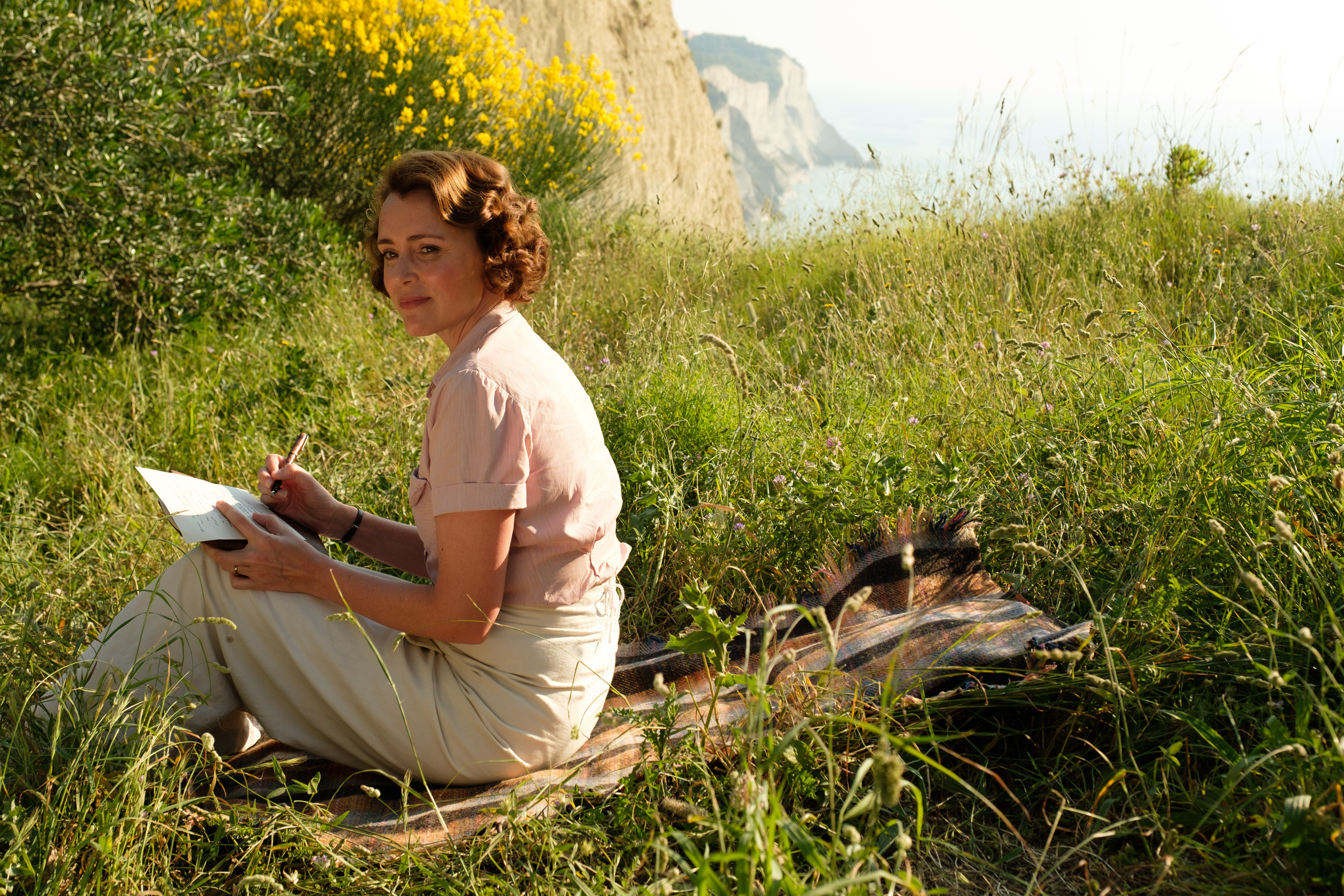 girl in a field with cliff in the background, writing
