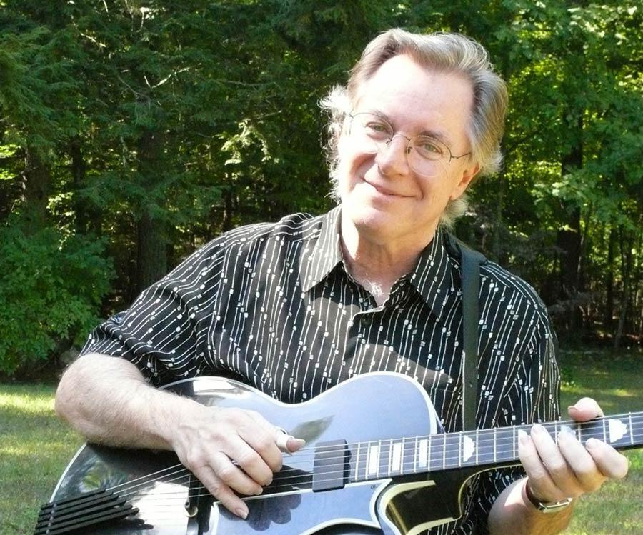 john sebastian playing a black guitar outdoors